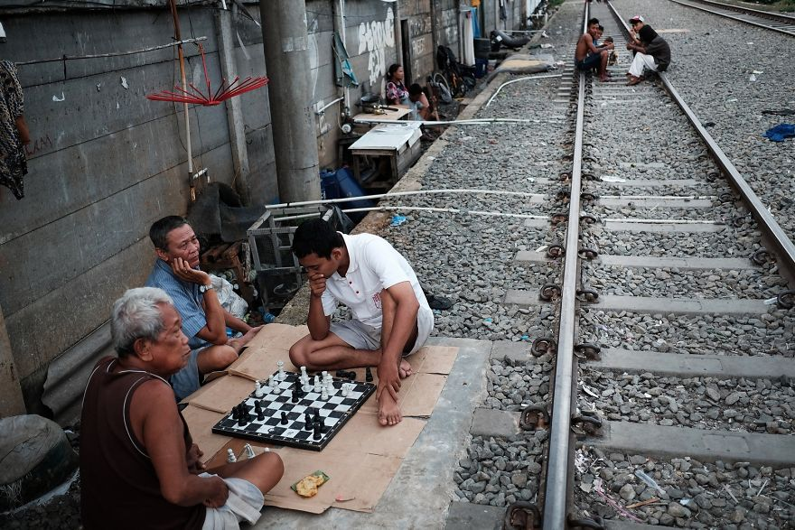 Men Are Playing Chess Next To The Active Railway Tracks. Trains Pass By Approximately Every 10-20 Minutes