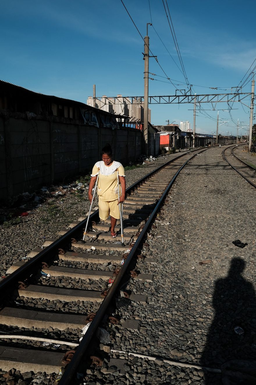 Woman With One Leg Is Walking On The Active Railway Tracks In A Slum Area Next To Jakarta Kota Train Station
