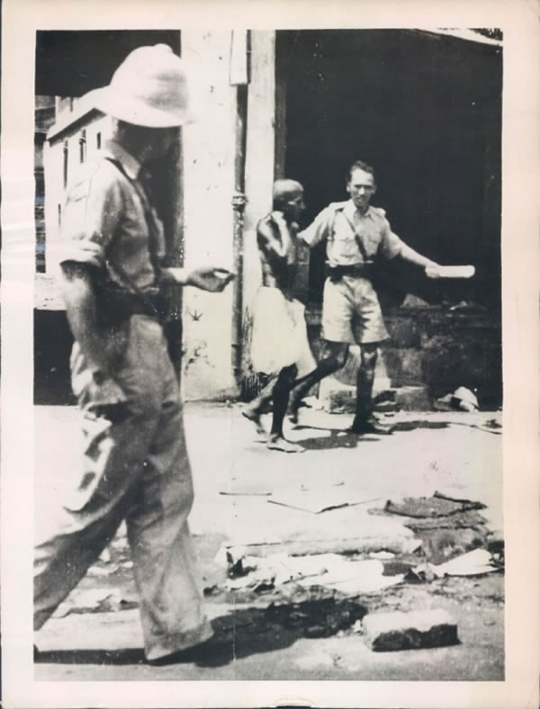 An Indian soldier leads away a Hindu rioter in a debris strewn street of Bombay (Mumbai) - 1946