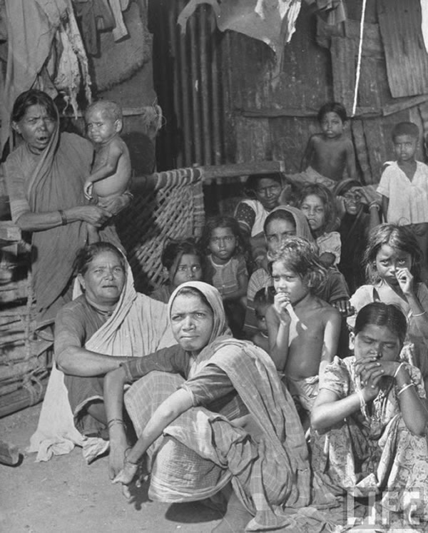 Indian women & children sitting in the alley between shacks in the Chawls