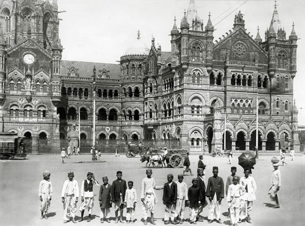 Young boys pose in front of Bombay's Victoria Terminus railway station, circa 1910
