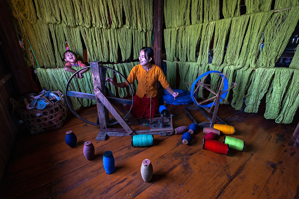 A women weaving inside a house with her daughter enjoying in Inle lake, Myanmar