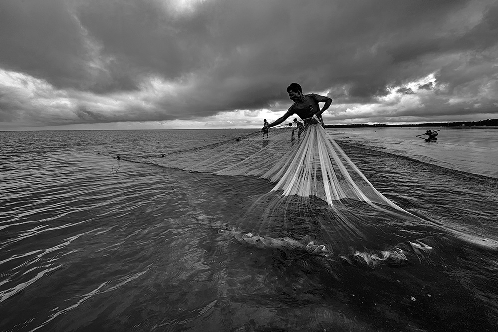 Fishermen in action on an overcast day in Udaypur beach, Odisha-West Bengal Border