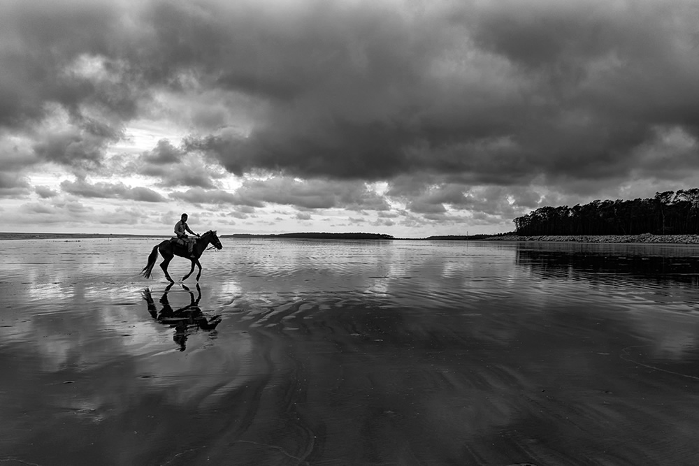 Horseman riding the reflecting beach of Udaypur after rain